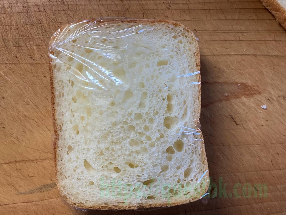 クリームとフルーツをトッピングしたらパンをサンドしてラップできっちりくるむ